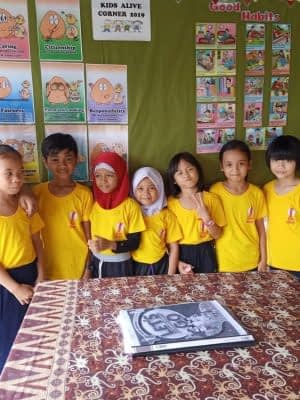Teacher Lina @ the Kids Alive! Corner with students in their bright KA! T-shirts.